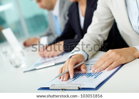 Close-up of female hands with pen over business document in working environment