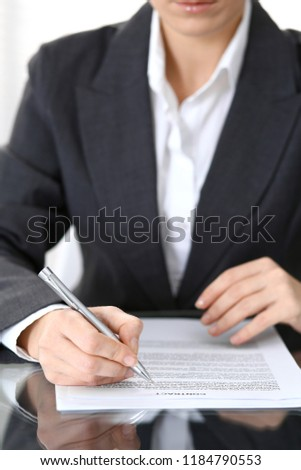 Close-up of female hands with pen over document of contact, business concept
