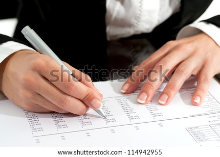 Close up of female hands with pen reviewing accounting document.