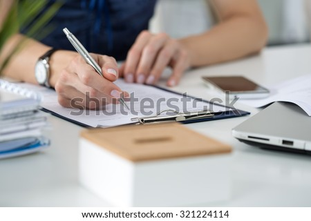 Close-up of female hands. Woman writing something  sitting at her office