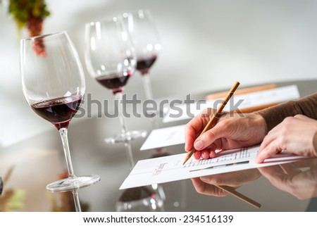 Close up of female hands writing notes at wine tasting.