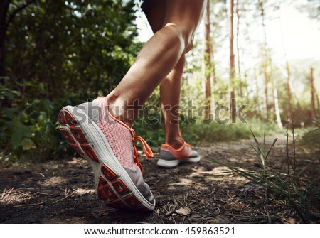 Close-up of female hiker feet walking on forest trail. Active woman backpacker traveling on the nature.  ストックフォト ©