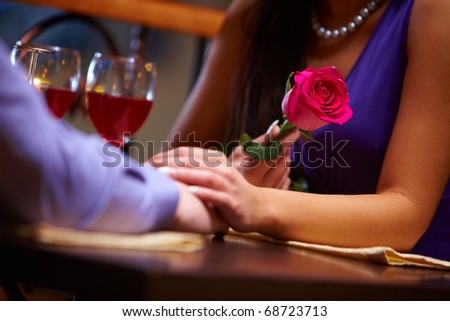 Close-up of female holding a red rose and her hand over male hand at  Valentine?s day