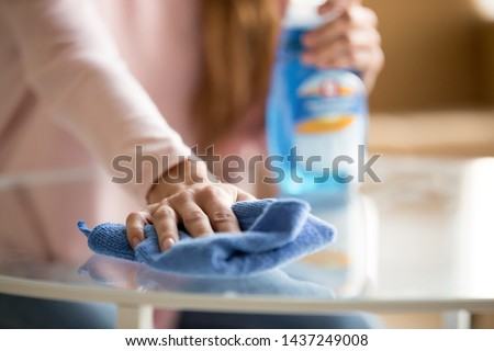 Close up of female housekeeper specialist hold blue duster cleaning glass table perform housekeeping job service, woman make daily house chores dust off using cloth with spray fluid detergent #1437249008