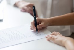 Close up of female job candidate hold pen put signature on official document in office, woman worker or applicant sign contract, close deal with business partner or client. Collaboration concept