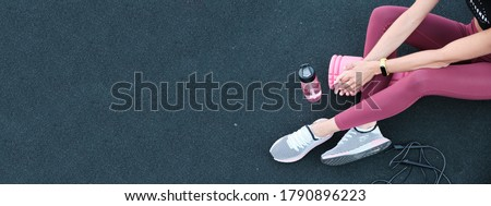 Close-up of female legs in trendy sportswear. Panoramic banner sportswoman sits on blue stadium cover texture background. Foto stock ©