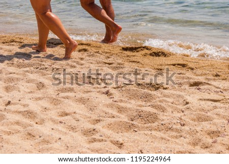 close-up of female legs walking along the edge of the surf #1195224964