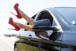 Close-up of female legs with red shoes of high heels. The woman is raising her feet through the window of the car