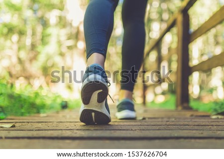 Close up of female legs with running shoes on wooden footpath in woods. Nature and sport healthy lifestyle concept. Сток-фото ©