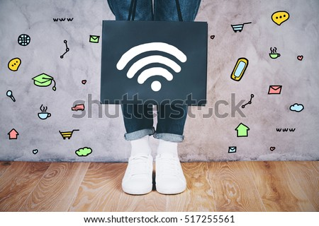 Close up of female legs with wi-fi signal icon on shopping bag and communication icons around on concrete wall. Social media concept