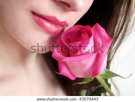 Close-up of female lips with pink rose