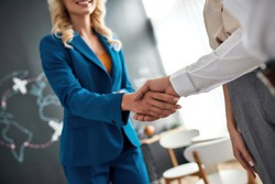 Close up of female manager and client handshaking after making a deal at the travel agency office. Tourism, travelling, business concept