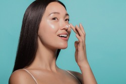 Close up of female model applying moisturizer cream to her nose. Woman applying moisturizer cream on her face against blue background.