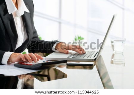Close up of female office worker's hands doing accounting with calculator and laptop.