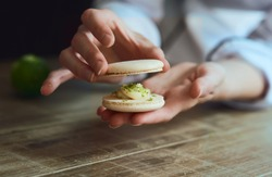 Close up of female pastry chef's hand cooking delicious macaroon. Close up, selective focus.