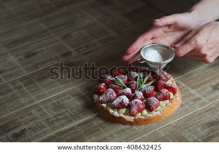 Close up of female pastry chef's hand decorating  top of delicious French strawberry cake. Cooking dessert in the kitchen. Close up, selective focus.