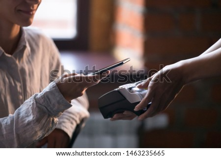 Close up of female restaurant or cafe client paying for order using cellphone with nfc technology, waitress holding card reader machine, woman customer make payment with cellphone contactless method