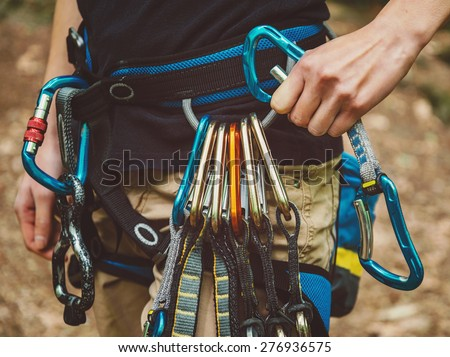 Close-up of female rock climber wearing safety harness with quickdraws and climbing equipment outdoor