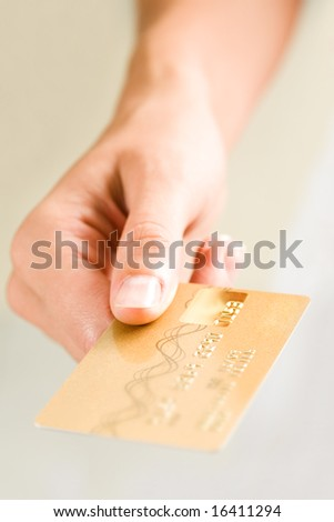 Close-up of femaleâ??s hand holding credit card and giving it to someone