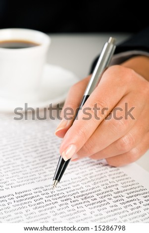Close-up of femaleâ??s hand holding pen over business document with cup of coffee near by