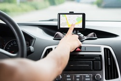 Close-up Of Female's Hand Using GPS Navigation Inside Car