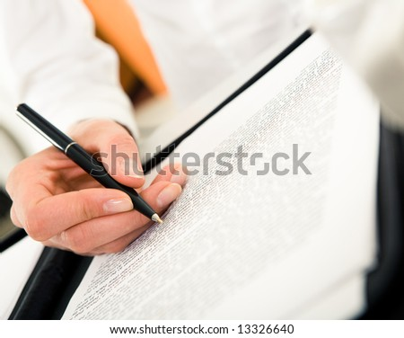 Close-up of female's hand with pen over paperwork