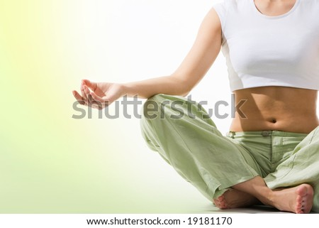 Close-up of female?s torso during meditation with legs crossed and hand being kept on her right knee
