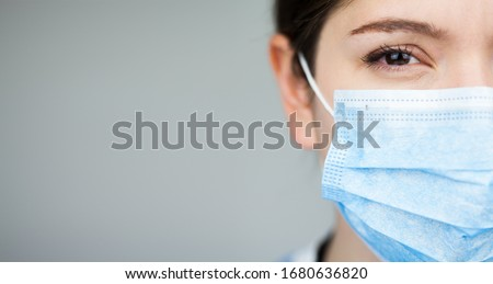 Close up of female UK EMS doctor's face,wearing blue PPE surgical protective mask,COVID-19 Coronavirus disease,global pandemic outbreak,deadly SARS-CoV-2 epidemic,grey copy space on left side of frame