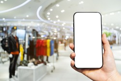 Close-up of female use Hand holding smartphone with empty blank white screen blurred images touch of Abstract blur of inside shopping complex background,shopping online concept.