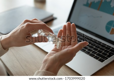 Close up of female worker sit in office clean hands use sanitizer against coronavirus pandemic, woman employee work on laptop sanitize with antibacterial liquid gel from covid-19 corona virus outbreak