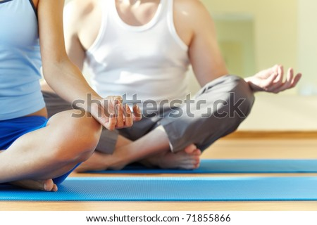 Close-up of feminine and masculine arms and crossed legs during meditation