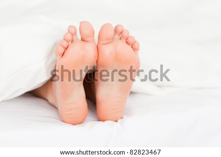 Close up of feminine feet in a bed