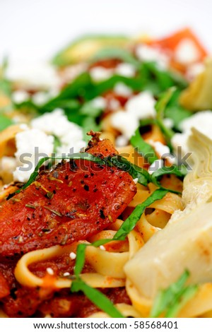Close-up of Fettuccine topped with fresh tomatoes and artichoke hearts sauteed with assorted herbs and olive oil, garnished with julienned basil leaves