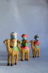 Close-up of figures of the Three Wise Men from the East, with a hygienic mask to protect themselves from Covid-19. Concept of Christmas, safety and precaution against Covid-19. Vertical and copy space