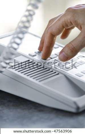 Close up of fingers dialing a desktop telephone