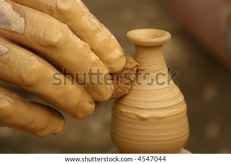 Close-up of fingers making pottery on a wheel