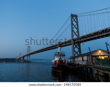 Close-up of fire station and fireboat tied up at dock in San Francisco Bay under the Bay Bridge at twilight