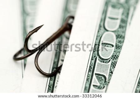 Close-up of fishing hook amongst US dollar bills