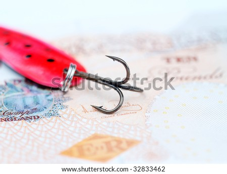 Close-up of fishing hook resting on UK bank note
