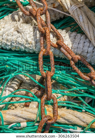 Close-up of fishing nets stacked in the harbor, paying particular attention to the colors, textures, materials, details, knots, etc.