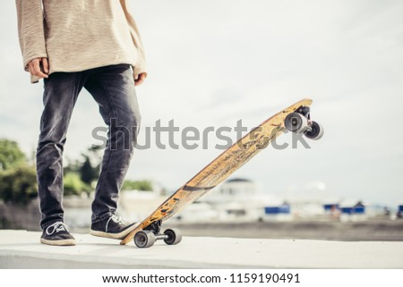 Close up of fit man ready to extreme ride wooden longboard skateboard. Good summer day for skateboarding
