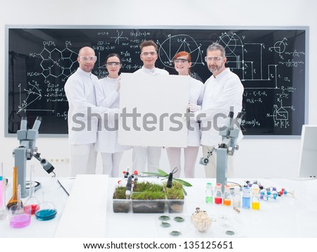 close-up of five smiling  scientists in a chemistry lab holding in hands an empty banner and confident looking in the camera with a blackboard on the background
