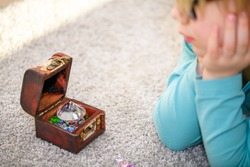 Close-up of five year old boy admiring a treasure chest full of multicolored gems. He has lined up gems on the floor.
