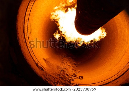 Close up of flame in rotary kiln during heating mode in cement plant Stockfoto ©