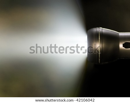 Close up of flashlight generating a beam of light - stock photo