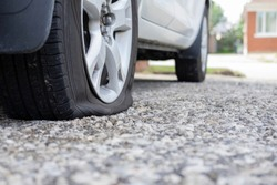 Close up of flat rear tire of white suv track car vehicle automobile punctured by nail. Summer day, residential street. Selective focus, depth of field, space for copy. Bad luck, accident concept.