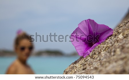 Close up of flower laying on a granite bolder and a young woman, or tourist in the Similan Islands, Andaman Sea, Thailand. - stock photo
