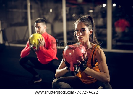 Close up of focused and motivated strong young fitness couple in sportswear crouching with the kettlebells reversed and doing squats in the gym. #789294622