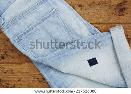 Close up of folded jeans on wooden floor