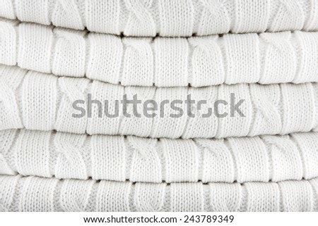 Close up of folded white knitted  plaid. Knitted fabric texture. Background.